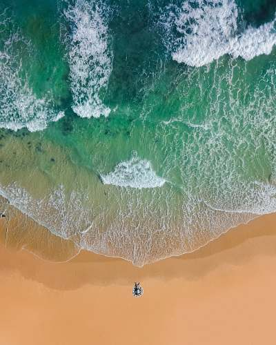 water top view photography of brown sand on beach with teal ocean water during daytime ocean