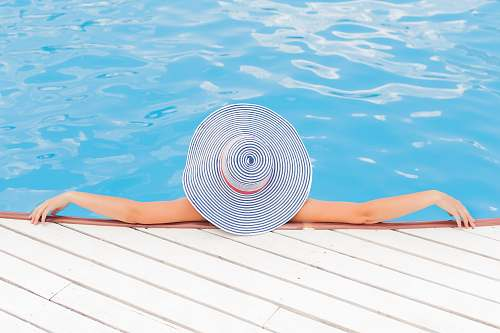 woman woman leaning on white concrete surface beside swimming pool during daytime pool