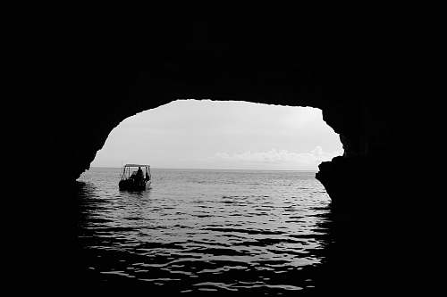 arch boat on body of water outside the cave grey
