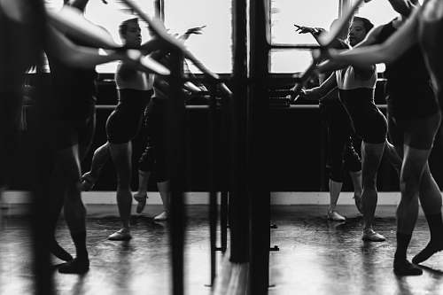 person grayscale photo of womens exercising in front of mirror dance