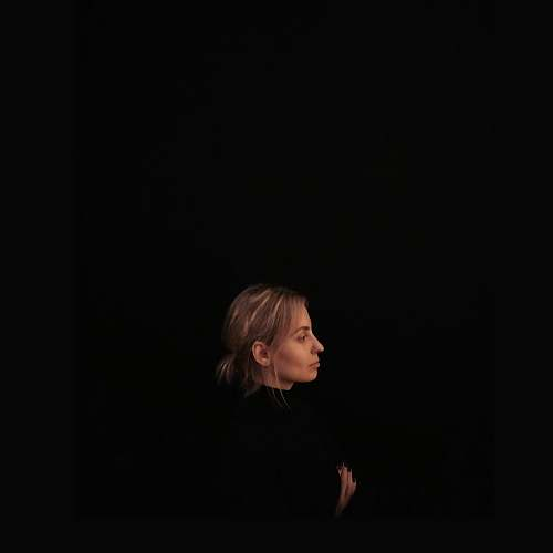 person minimalist photography of woman wearing black top facing to the side human