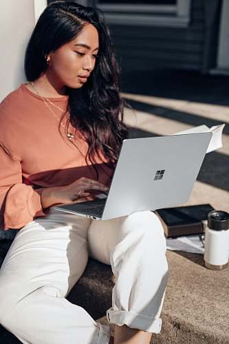electronics woman in orange long sleeve shirt and white pants sitting on floor using Surface Laptop  pc