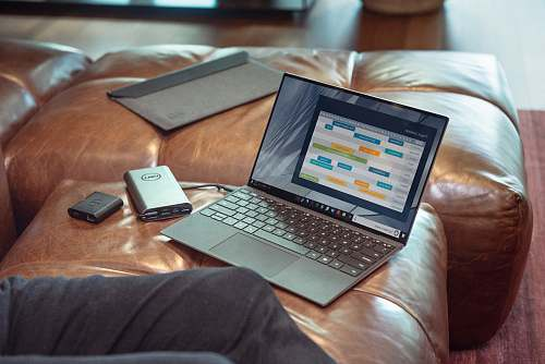 pc black and gray laptop computer on brown leather couch computer