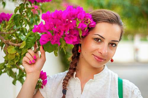 blossom woman wearing white top holding pink flower human