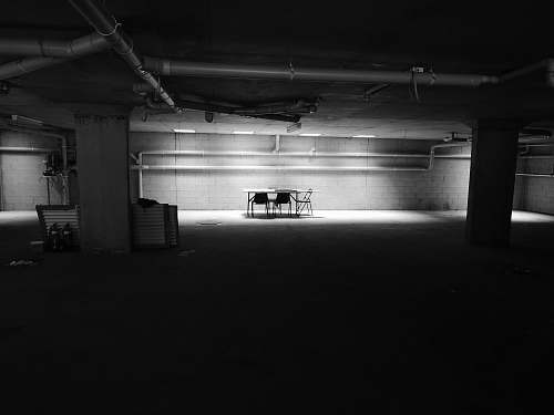 photo black-and-white table with chairs near wall in a dark room parking lot free for commercial use images