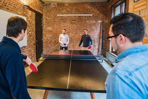 person four men playing table tennis ping pong