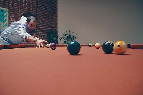 person man playing billiard near green leafed plants people