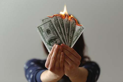 human a fan of fake American dollars on fire person