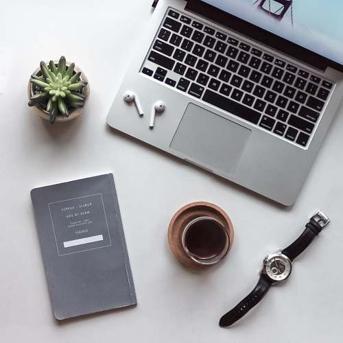 jewelry flat-lay photography of MacBook, coffee-filled cup, book, and wristwatch brooch