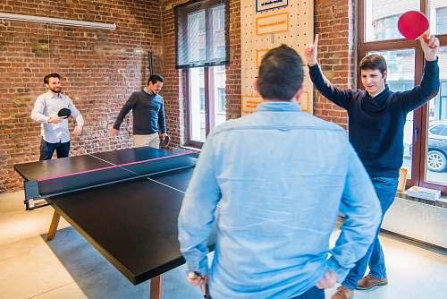 human four men playing table tennis ping pong