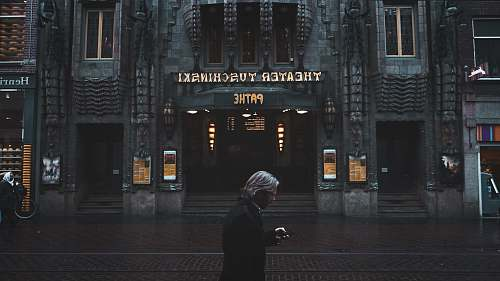 amsterdam man standing near Theater Tuschinski building human