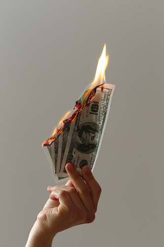 human person holding lighted dollar bills course
