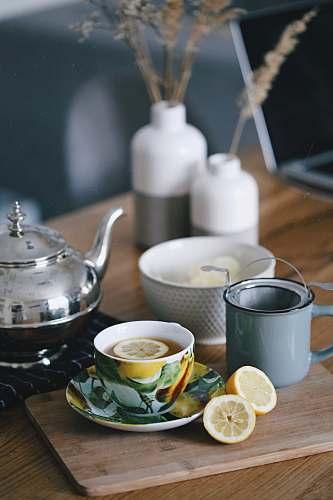 saucer gray teapot beside mug filled with tea and lemon on top of table tea