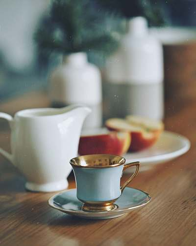 pottery selective focus photography of teacup beside two slices of apple cup