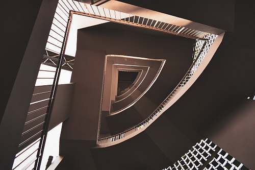 spiral low-angle photography of concrete stair building