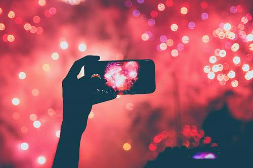 chile person taking a photo of fireworks using smartphoen hand